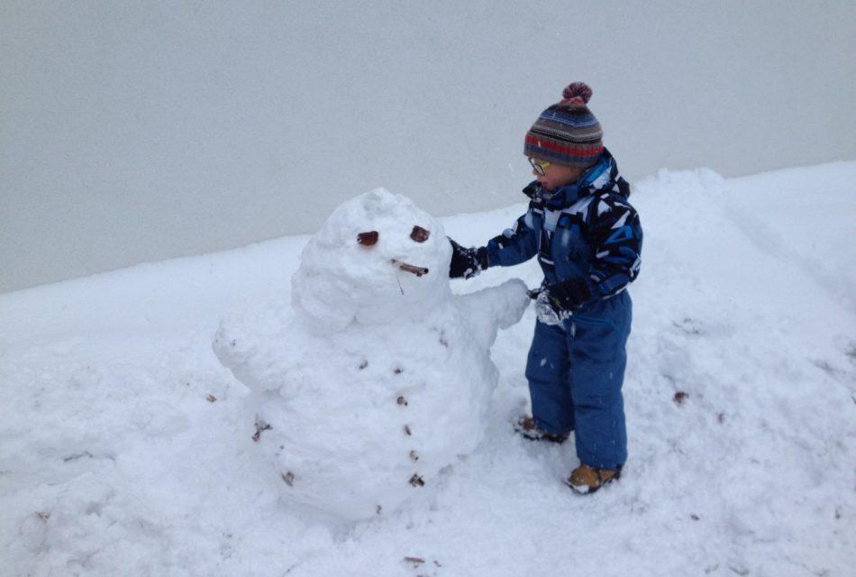 Schneemannbauen im Urlaub Spielplatz Kinder